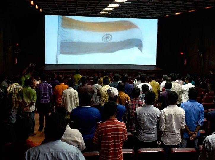 People stand up during national anthem at a theatre.