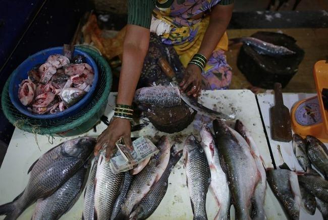 A vendor selling fish collects money from a customer at her stall at a market in Mumbai