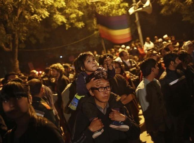 A gay rights activist carries a child on his shoulders as he attends a protest against a verdict by the Supreme Court in New Delhi