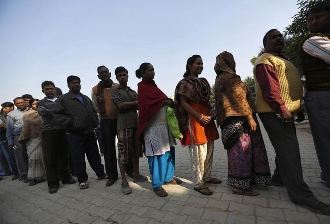 Voters line up in queue outside polling booth to cast vote during state assembly election in New Delhi