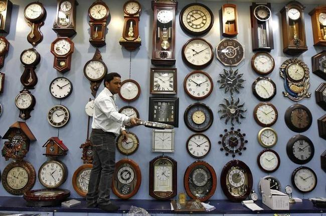 Ένας πωλητής δείχνει ένα ρολόι μέσα σε ένα εμπορικό κέντρο στην Καλκούτα και ένα ρολόι τοίχου σε έναν πελάτη σε ένα κατάστημα ρολογιών