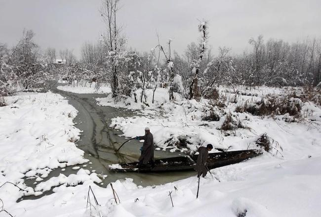 Kashmiri men try to push their boat through the waters of Anchar Lake after heavy snowfall in Srinagar