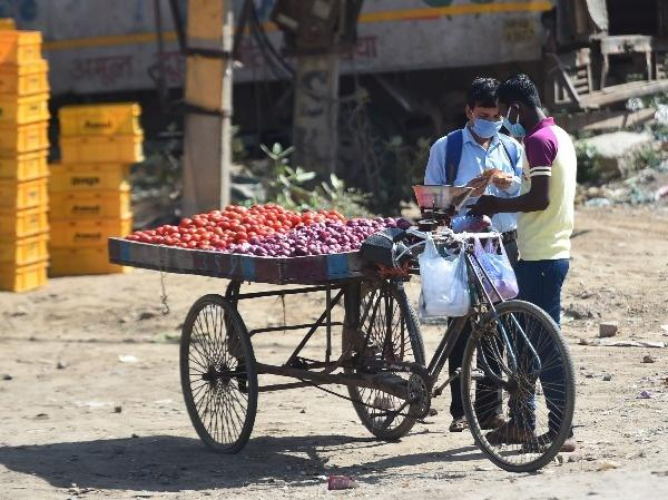 A man buys vegetables from a cycle rickshaw hawker during the first day of a 21-day government-imposed nationwide lockdown
