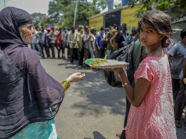 Homeless people receive free food offered by the Telangana state governement.